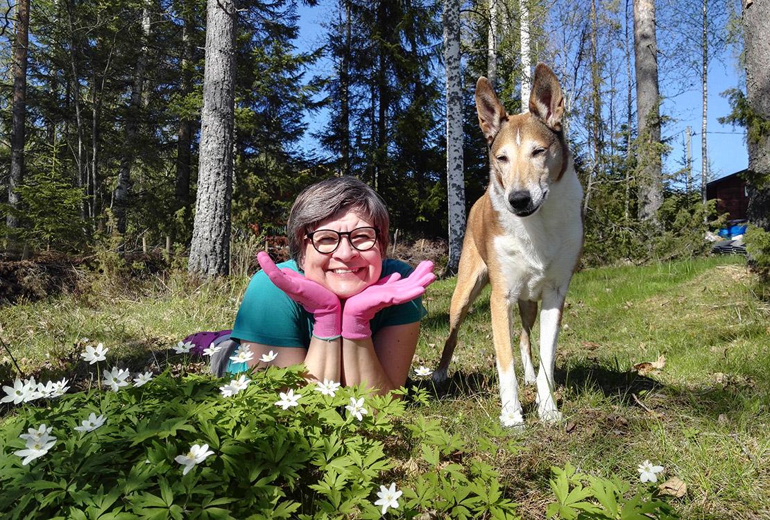 Anne Korhonen ja hänen koiransa valkovuokkojen ympäröimänä kesämökillä.