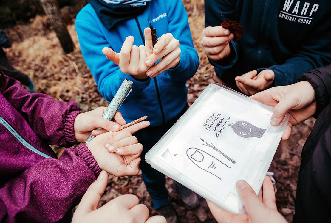 Oppilaat miettivät ratkaisua kuvalliseen tehtävään metsässä.