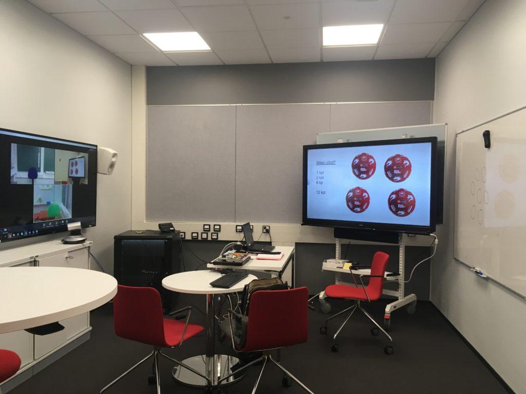 Kuvassa on pienehkö opetushuone, jossa on web-kamera ja kaksi suurta näyttöä sekä valkoisia pöytiä ja punaisia tuoleja.