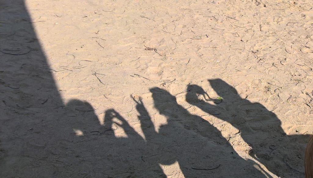 Kuvassa on varjokuvia oppilaista rantahiekalla.