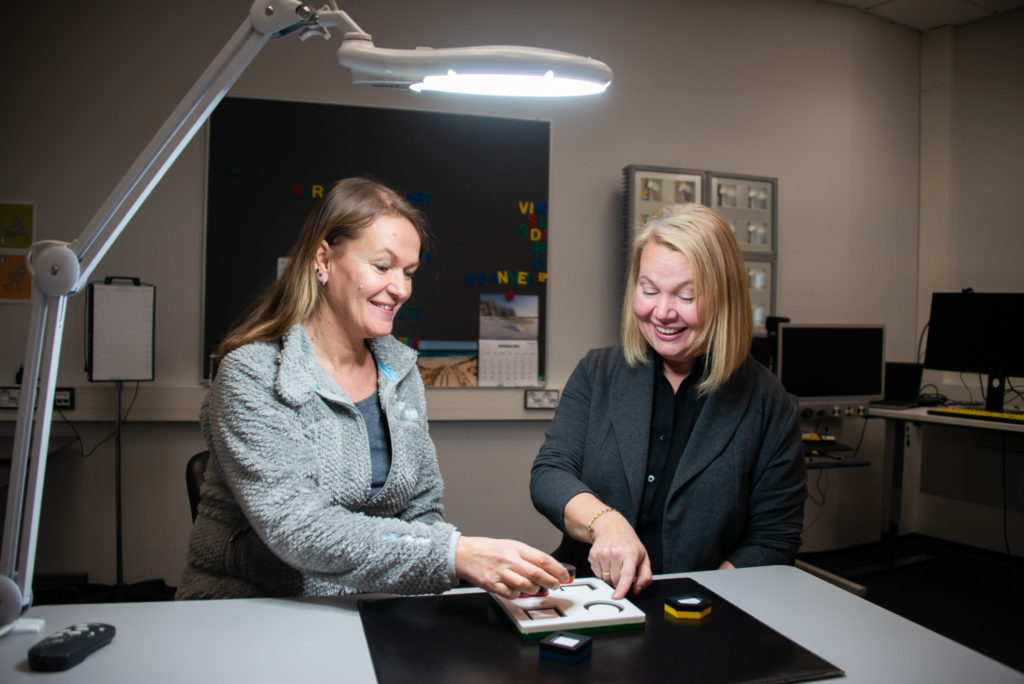 Näönkäytönohjaaja Piia Puolanen ja ohjaava opettaja Päivi Lång istuvat pöydän ääressä ison, kirkkaan lampunvalon alla.