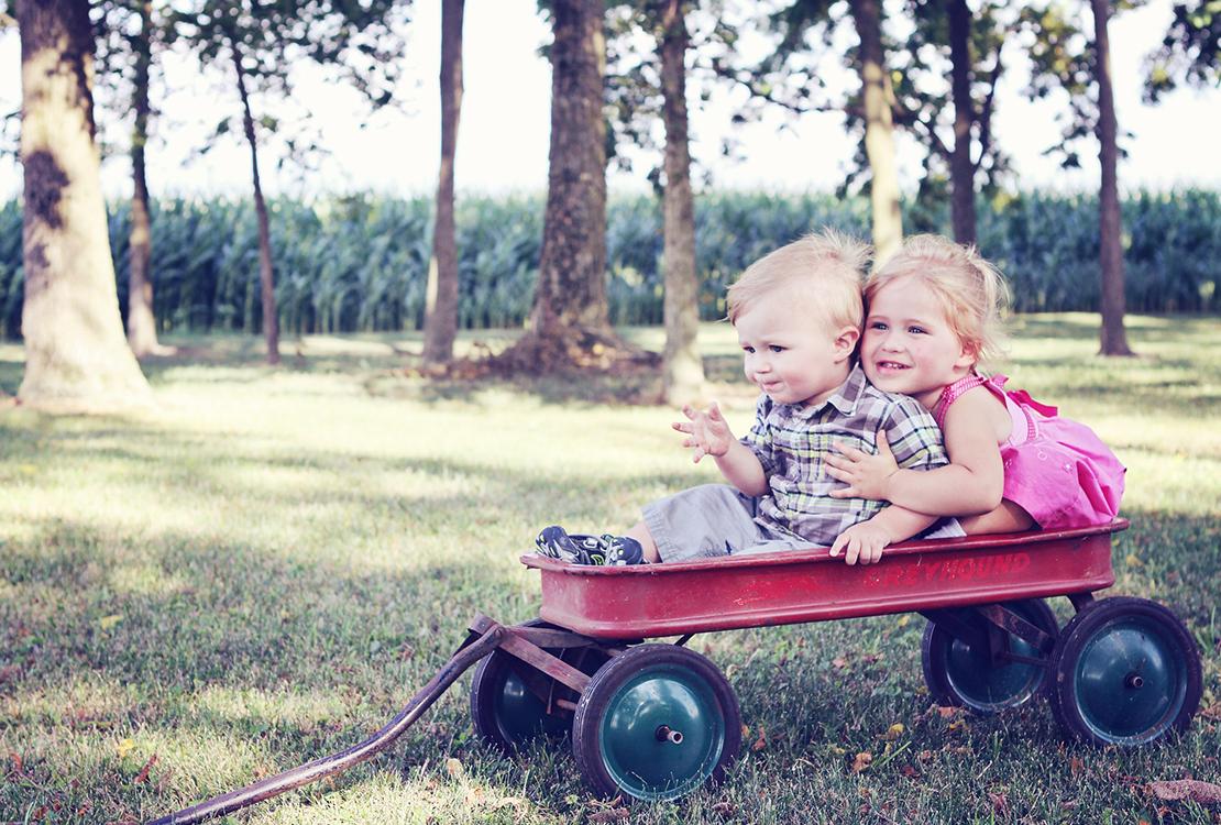 Lapset istuvat sylikkäin leikkivaunussa pihanurmella.
