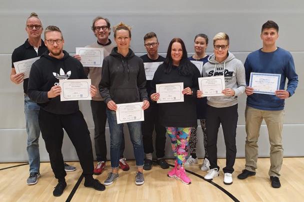 Kuvassa on yhdeksän henkilöä, jotka seisovat käsissään todistukset siitä, että ovat valmistuneet MAPA-kouluttajiksi. Yksi heistä, Klaus Tanttu, on valmistunut MAPA-erityistason kouluttajaksi.